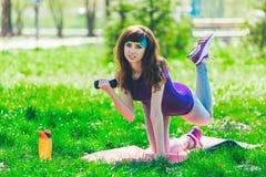Fille de forme physique en parc et occupée dans de divers exercices avec l'haltère et le tapis la brune entre pour des sports deh Photos libres de droits