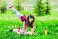 Fille de forme physique en parc et occupée dans de divers exercices avec l'haltère et le tapis la brune entre pour des sports deh Photo libre de droits