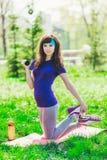 Fille de forme physique en parc et occupée dans de divers exercices avec l'haltère et le tapis la brune entre pour des sports deh Photographie stock
