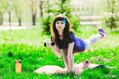 Fille de forme physique en parc et occupée dans de divers exercices avec l'haltère et le tapis la brune entre pour des sports deh Images libres de droits