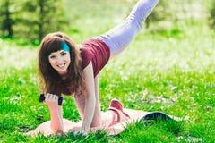 Fille de forme physique en parc et occupée dans de divers exercices avec l'haltère et le tapis la brune entre pour des sports deh Photographie stock libre de droits