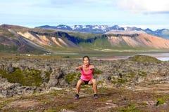 Fille de forme physique s'exerçant dehors faisant la posture accroupie de saut Photo stock