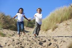 Fille de garçon blond et de chemin mélangé exécutant à la plage Photo libre de droits