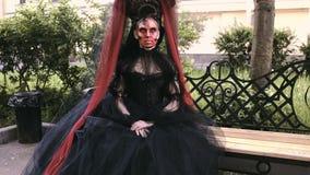 Fille de Halloween dans la sorcière s'asseyant sur un banc dans le mystère de forêt de parc de ville et le concept d'horreur banque de vidéos