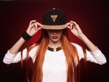 Fille de hip-hop dans le chapeau avec de longs cheveux rouges photos libres de droits