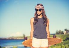 Fille de hippie avec les lunettes de soleil de port de panneau de patin photo stock