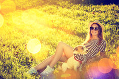 Fille de hippie avec son chien se trouvant sur l'herbe Photo libre de droits