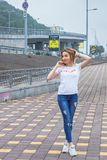 Fille de hippie utilisant le T-shirt, les jeans vides et la casquette de baseball blancs posant contre le mur rugueux de rue, por photo stock