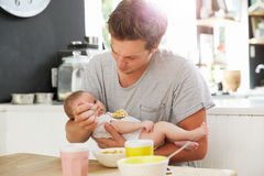 Fille de Holding Newborn Baby de père à la table de cuisine Image stock