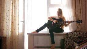 Fille de jeune adolescent jouant la guitare acoustique à la maison banque de vidéos