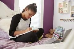 Fille de jeune adolescent s'asseyant sur son écriture de lit dans un carnet images stock