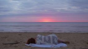Fille de jeune femme dans une robe blanche s'étendant dans le premier plan sur une couverture et appréciant le ciel rougeoyant ra clips vidéos