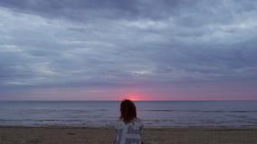 Fille de jeune femme dans une robe blanche se reposant dans le premier plan sur une couverture et appréciant le ciel rougeoyant r banque de vidéos