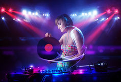 Fille de jockey de disque jouant la musique avec des effets de faisceau lumineux sur l'étape illustration stock