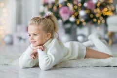 Fille de Joyeux Noël et bonnes fêtes de Litl jouant près de l'arbre de Noël photos libres de droits