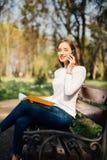 Fille de l'adolescence à l'aide d'un téléphone intelligent et textotant se reposer avec le carnet dans un banc d'un parc urbain Images stock