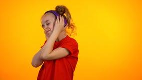 Fille de l'adolescence adorable écoutant la chanson préférée dans des écouteurs et dansant, passe-temps photos libres de droits