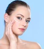 Fille de l'adolescence appliquant la crème sur la peau autour des yeux Photographie stock