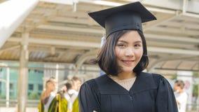 Fille de l'adolescence asiatique avec le tissu de robe d'obtention du diplôme avec se sentir heureux Photos libres de droits