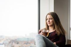 Fille de l'adolescence avec la tasse de thé regardant par la fenêtre Photographie stock
