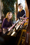 Fille de l'adolescence avec le frère par le piano image stock