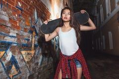 Fille de l'adolescence avec le panneau de patin, mode de vie urbain Photographie stock libre de droits