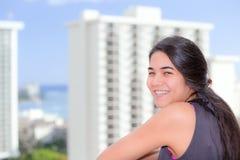 Fille de l'adolescence Biracial se tenant sur le balcon ayant beaucoup d'étages de la ville urbaine Image stock
