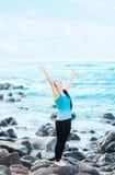 Fille de l'adolescence Biracial sur des roches par l'océan félicitant Dieu Images stock