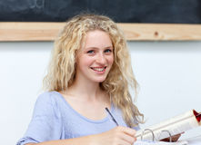 Fille de l'adolescence blonde étudiant dans la bibliothèque Photo libre de droits