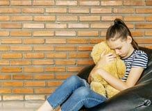 Fille de l'adolescence caucasienne bouleversée s'asseyant dans jouet brun d'ours de nounours d'étreinte de chaise de sac de haric photos libres de droits