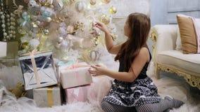 Fille de l'adolescence considérant un cadeau Temps de Noël banque de vidéos
