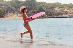 Fille de l'adolescence courant à la mer avec le panneau rose de corps Photos libres de droits