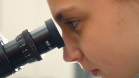 Fille de l'adolescence d'école au laboratoire étudiant la biologie, regardant par le microscope Plan rapproché clips vidéos