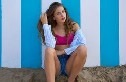 Fille de l'adolescence d'été de brune dans le mur de rayures bleues photographie stock