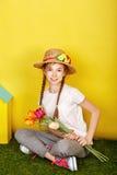 Fille de l'adolescence dans le chapeau de paille tenant des fleurs de ressort Image libre de droits