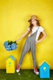 Fille de l'adolescence dans le chapeau de paille tenant des fleurs de ressort Photos stock