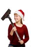 Fille de l'adolescence dans le chapeau de Santa avec l'aspirateur Images libres de droits