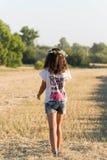 Fille de l'adolescence dans une guirlande de walketh de marguerites dans le domaine images libres de droits