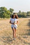 Fille de l'adolescence dans une guirlande de walketh de marguerites dans le domaine photo libre de droits