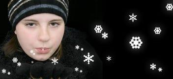 Fille de l'adolescence de l'hiver soufflant la neige magique Images stock