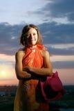Fille de l'adolescence de sourire avec le chapeau et pareo sur le coucher du soleil Photographie stock
