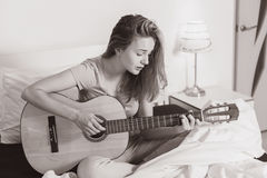 Fille de l'adolescence de sourire jouant sur la guitare sur le lit à la maison Photo stock