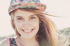 Fille de l'adolescence de sourire utilisant le chapeau floral Image libre de droits