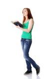 Fille de l'adolescence debout affichant un livre. Photo stock