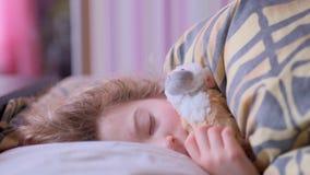 Fille de l'adolescence dormant sur le lit avec un singe de jouet banque de vidéos