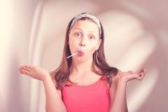 Fille de l'adolescence drôle mangeant le lollypop Photos libres de droits