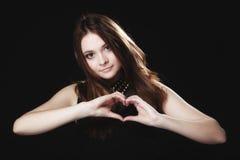 Fille de l'adolescence faisant le symbole d'amour de forme de coeur avec des mains Image libre de droits