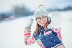 Fille de l'adolescence heureuse d'hiver jouant dans la boule de neige de lancement de neige Image libre de droits