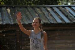 Fille de l'adolescence heureuse sous la pluie d'été Images stock