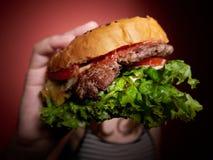 Fille de l'adolescence mangeant un hamburger Image stock